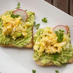 Torras com pasta de abacate, rodelas de rabanete e ovos mexidos