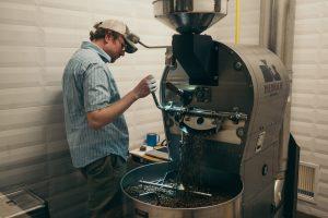 Homem realizando uma etapa de moagem no processo produtivo do café.